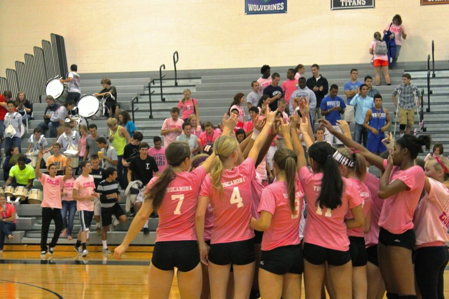 The varsity volleyball team celebrates defeating Heritage 3-0 in the 4th annual Dig Pink game. Photo by Rikki Pepino.