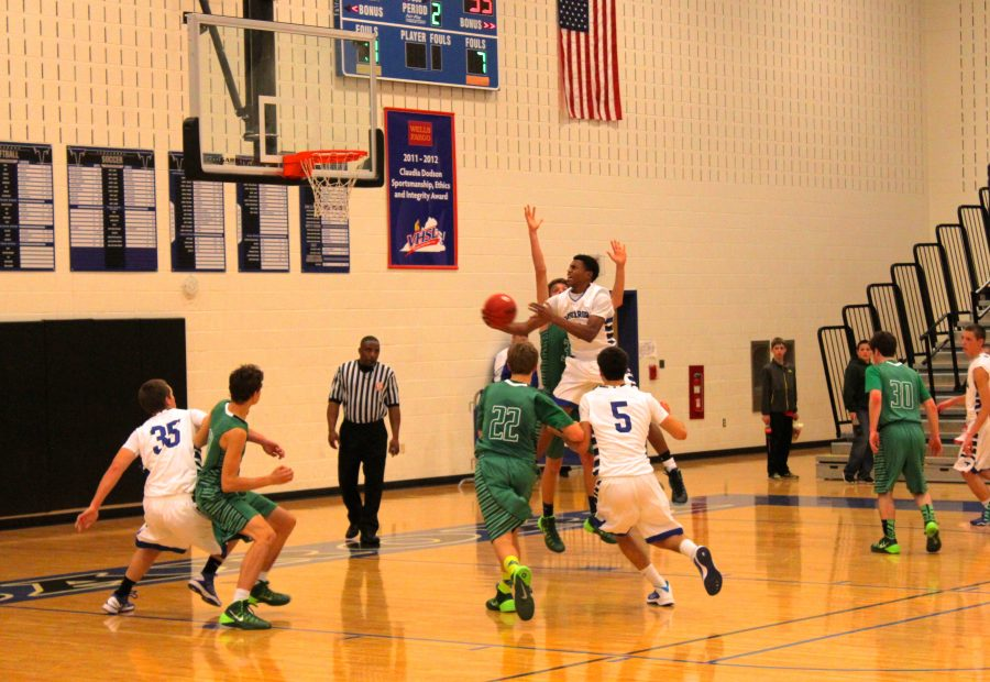 Senior guard Jordan Roach attempts to make a lay-up. At the end of the game, Roach scored 14 points and 11 rebounds. Photo credit: Rikki Pepino