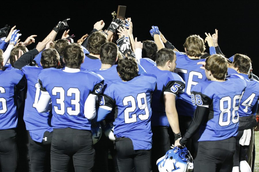 The+varsity+football+Huskies+celebrate+their+win+against+Briar+Woods+High+School++last+Friday%2C+November+7th%2C+as+they+hold+up+the+District+Championship+plaque+in+a+huddle.%0A%0APhoto+Credit%3A+Hanna+Duenkel