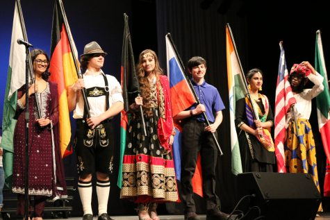 """uniors Mitya Gull, Bryce Treichel, Dolhan Mohammadi, Helen Varghese and sophomore Luke Hubbard greet the crowd after the models perform on stage with their flags. """"I was representing Germany for U-Nite. Germany has a rich history and has unique cultural traditions and clothing. My family was originally from there in the 1800's. My favorite tradition of Germany is the lederhosen they wear,"""" said Treichel."""