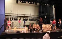 The crew fixes the on-stage lights.